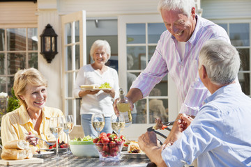 Smiling senior couples drinking wine and enjoying lunch on sunny patio