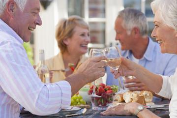 Senior couples drinking wine and enjoying lunch on sunny patio