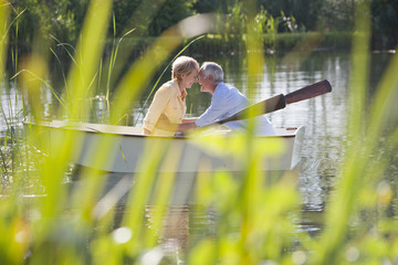 Senior couple face to face in rowboat on sunny lake