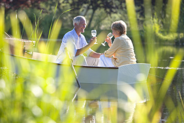Senior couple drinking wine in rowboat on sunny lake