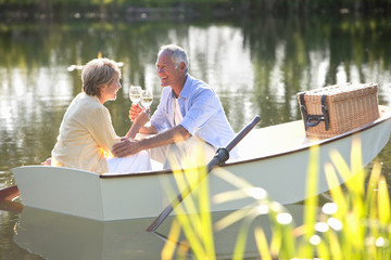 Senior couple drinking wine on rowboat on sunny lake