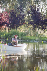 Senior man fishing in rowboat on sunny lake