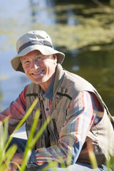 Portrait of smiling senior man at sunny lake