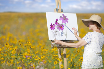 Senior woman painting in sunny wildflower meadow