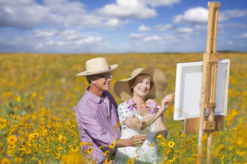 Smiling senior couple painting in sunny wildflower meadow