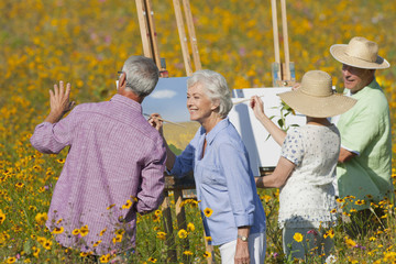 Senior couples painting in sunny wildflower meadow