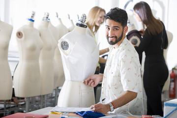 Fashion design student working on garment on mannequin