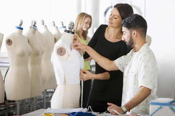 Fashion designer and student working on garment on mannequin