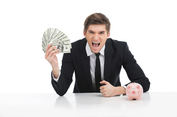 Portrait of young businessman holding dollars.