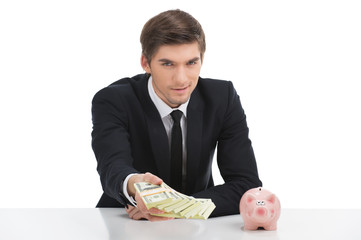 Business man holding dollar bills, isolated on white.