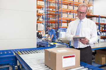 Supervisor using digital tablet next to cardboard box on production line in distribution warehouse