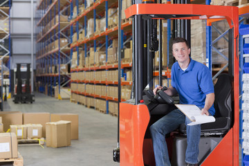 Portrait of smiling worker sitting in forklift with paperwork in distribution warehouse