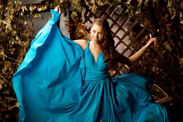 Beautiful woman in long blue dress. Young girl in luxury fashion