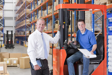 Portrait of smiling supervisor and worker in forklift in distribution warehouse
