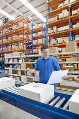 Smiling worker scanning box on production line in distribution warehouse