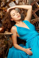 Beautiful woman in a long blue dress. Young girl in luxury fashi