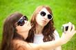 Duckface. Selfie. Two young trendy girls doing selfie. A couple
