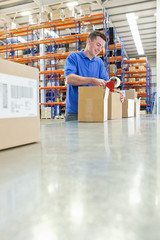 Worker taping cardboard boxes on production line in distribution warehouse