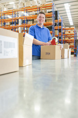 Portrait of smiling worker taping cardboard boxes on production line in distribution warehouse