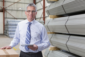 Portrait of smiling supervisor with digital tablet next to steel bars in warehouse