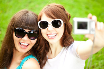 Selfie. Two young trendy girls doing selfie. A couple of friends