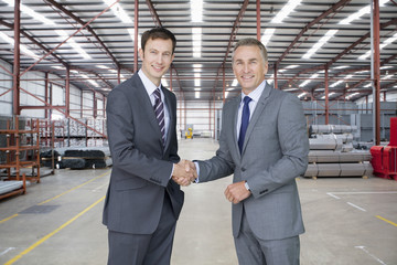 Portrait of smiling businessman handshaking in warehouse