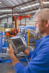 Close up of worker controlling robotic machinery lifting steel fencing on production line in manufacturing plant
