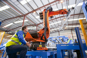 Technician controlling robotic machinery lifting steel fencing on production line in manufacturing plant