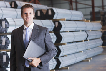 Portrait of confident businessman in front of steel tubing in warehouse