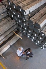 Bank manager and businessman shaking hands near steel tubing in warehouse