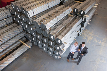 Bank manager and businessman meeting near steel tubing in warehouse