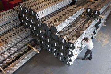 Frustrated businessman leaning on steel tubing in warehouse