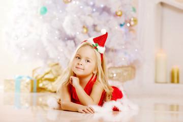 Beauty little Santa girl near the Christmas tree.  Happy girl wi