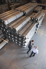 Businessmen talking near steel tubing in warehouse