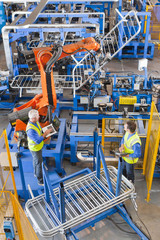 Workers watching robotic machinery lift steel fencing on production line in manufacturing plant