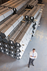 Portrait of confident businessman near steel tubing in warehouse