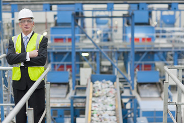 Portrait of serious businessman standing on platform above conveyor belt in recycling plant
