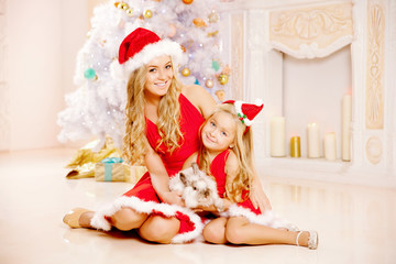 Mother and daughter dressed as Santa celebrate Christmas. Family