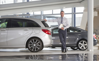Portrait of smiling salesman holding brochure and leaning on car in car dealership showroom