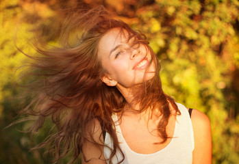 Beautiful smiling woman in a field at sunset with flying hair