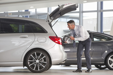 Man with brochure looking into hatchback of car in car dealership showroom