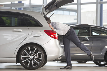 Man looking into hatchback of car in car dealership showroom