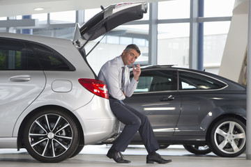 Portrait of worried salesman leaning on car in car dealership showroom