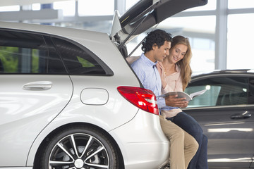 Couple looking at brochure in hatchback of car in car dealership showroom