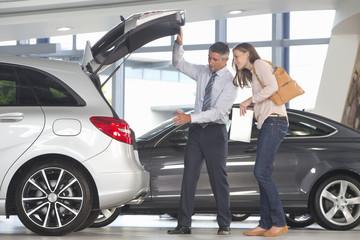 Salesman showing customer hatchback of car in car dealership showroom