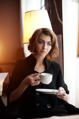 Young beautiful woman in a cafe. Modern trendy blondy girl in re