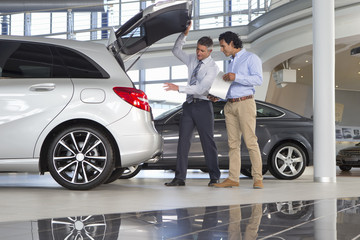 Salesman and customer looking into hatchback of car in car dealership showroom