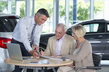 Salesman presenting contract to couple at table in car dealership showroom