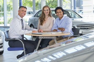 Portrait of smiling salesman and couple at table in car dealership showroom