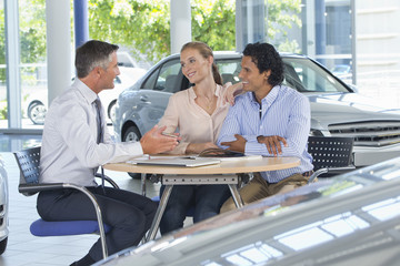 Salesman talking to couple at table in car dealership showroom